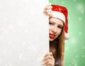 Young woman in santa claus hat with christmas card beautiful suit holding greeting or advertisement on green background falling Royalty Free Stock Photo