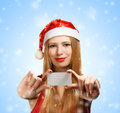 Young woman in santa claus hat with christmas greeting card beautiful suit holding or advertisement on blue background falling Royalty Free Stock Photos