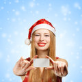 Young woman in santa claus hat with christmas greeting card beautiful suit holding or advertisement on blue snowfall background Royalty Free Stock Photos
