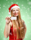 Young woman in santa claus hat with christmas invitation card beautiful suit holding greeting or advertisement on green background Royalty Free Stock Image