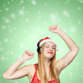 Young woman in santa claus hat and headphones take pleasure from music on green background with snowfall Royalty Free Stock Images