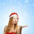 Young woman in santa hat blows on open hand Royalty Free Stock Photo