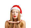 Young woman in santa hat blows on open hands beautiful claus isolated white background Royalty Free Stock Images