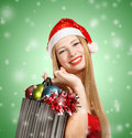 Young woman in santa hat with christmas attributes and gifts beautiful claus suit holding box new year on green background Royalty Free Stock Photo