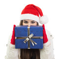 Young woman with santa hat holding big blue gift box cute happy caucasian brunette hiding behind it looking at camera isolated on Stock Photo