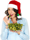 Young woman in santa hat holding a bowl of brussel sprouts dslr royalty free image eating cooked brussels from glass wearing red Royalty Free Stock Image