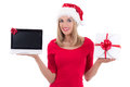 Young woman in santa hat holding notebook and present over white background Royalty Free Stock Photography