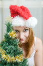Young woman  in Santa hat near Christmas tree Royalty Free Stock Photo