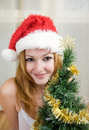 Young woman in Santa hat near Christmas tree Stock Photos