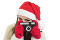 Young woman with santa hat using analogue camera happy caucasian brunette and red gloves looking at isolated on white Stock Images