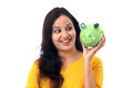 Young woman saves money in piggy bank cheerful indian Royalty Free Stock Image