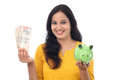 Young woman saves money in piggy bank indian Royalty Free Stock Photo
