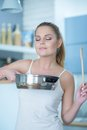 Young woman savoring the smell of her cooking holding up a stainless steel pot in air smelling contents with a look Stock Image