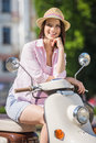 Young woman on scooter cheerful girl sitting in european city Stock Images