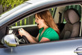 Young woman screaming while driving the car hands on steering wheel Stock Images