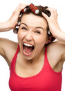 Young woman screaming terror holding her head hands wearing hair rollers isolated over white Royalty Free Stock Photos