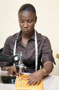 Young woman seamstress this sitting focused on her work is sewing a loincloth Royalty Free Stock Photography