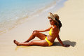 Young woman seating down on a sandy beach and sun bathing in yellow swimsuit hat sunglasses sunny summer day Royalty Free Stock Photos