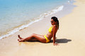 Young woman seating down on a sandy beach and sun bathing in yellow swimsuit sunglasses sunny summer day Stock Images