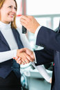 Young woman and seller with auto in car dealership or salesman customer they shaking hands hands over the keys seal the purchase Stock Images