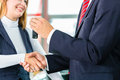 Young woman and seller with auto in car dealership or salesman customer they shaking hands hands over the keys seal the purchase Royalty Free Stock Image