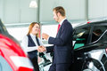 Young woman and seller with auto in car dealership or salesman customer they shaking hands hands over the keys seal the purchase Stock Photos