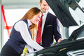 Young woman and seller with auto in car dealership or salesman female client or customer presenting the engine performance of new Royalty Free Stock Photos