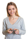 Young woman sending text message laughing at camera after writing a Royalty Free Stock Photo