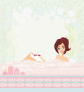 Young woman shaving her legs in bath. Royalty Free Stock Photography