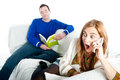 Young woman shocked at something on the phone whilst her boyfriend reads man and women relaxing home sofa Stock Photo