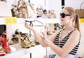 Young woman in the shoe shop sunglasses choosing summer shoes Royalty Free Stock Image