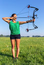 Young woman shooting arrow of compound bow Royalty Free Stock Photo