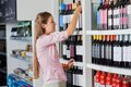 Young woman shopping for alcohol side view of at supermarket Stock Photo