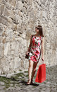 Young woman with shopping bag in a city street beautiful dress red walking on cobblestoned old near stoned wall Royalty Free Stock Photo