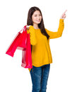Young woman with shopping bag and finger point up