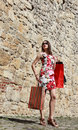 Young woman with shopping bags in a city street beautiful dress posing on cobblestoned old near stoned wall Royalty Free Stock Photography