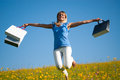 Young woman with shopping bags jumping in a meadow Stock Image