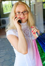 Young woman with shopping bags and mobile phone Stock Images