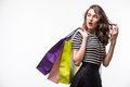 Young woman with shopping bags over white background screaming and wondering Royalty Free Stock Photo