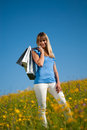 Young woman with shopping bags standing in a meadow Stock Image