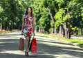 Young woman with shopping bags walking in a park Royalty Free Stock Photos