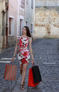 Young woman with shopping bags walking in a small cobblestone street in a city Stock Image