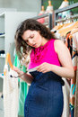 Young woman shopping in fashion department store looking at expensive price tag while boutique or Royalty Free Stock Photography