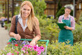 Young woman shopping  flowers in garden center Royalty Free Stock Photo