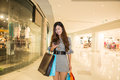 Young woman shopping in mall carrying bags and smiling Royalty Free Stock Images
