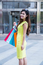 Young woman shopping in mall carrying bags and smiling Stock Photo