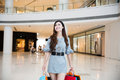 A young woman shopping in mall carrying bags and smiling Royalty Free Stock Image