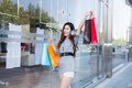 Young woman shopping in mall carrying bags and smiling Royalty Free Stock Photography