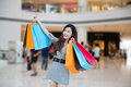 A young woman shopping in mall carrying bags and smiling Stock Image