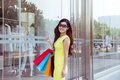Young woman shopping in mall carrying bags and smiling Stock Photos